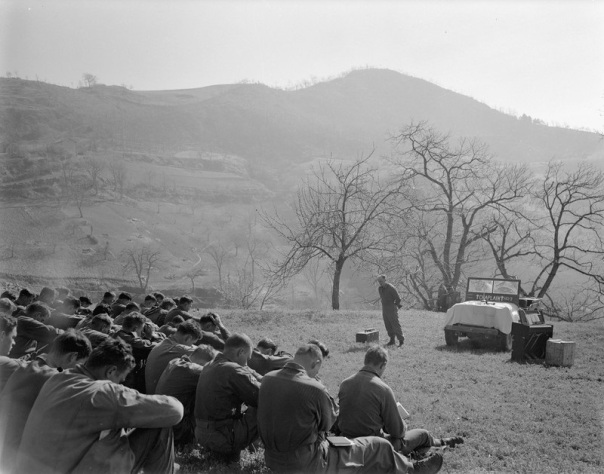 """One of many Easter services held on Appenine mountainsides by the Tenth Mountain Division April 1, 1945; conducted by Caplain William H. Bell for the 605th Artillery Battalion at Rocca Pitigliano. A large group of soldiers sit in a grassy open field with heads bowed. Before them stands the chaplain with a box beside him, a jeep marked beneath the windshield with 'Chaplain' in between two crosses, and a portable pump organ."""