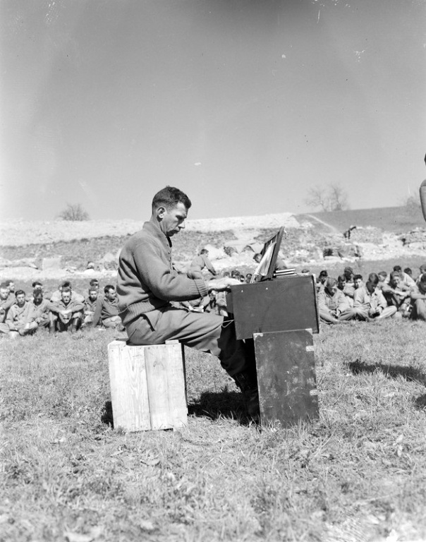 """Tenth Mountain Division Cpl. Ralph Squires plays the organ during the 605th Artillery Battalion Protestant Easter service held April 1, 1945, at Rocca Pitigliana, Italy. Worshipers sit on grass listening."""
