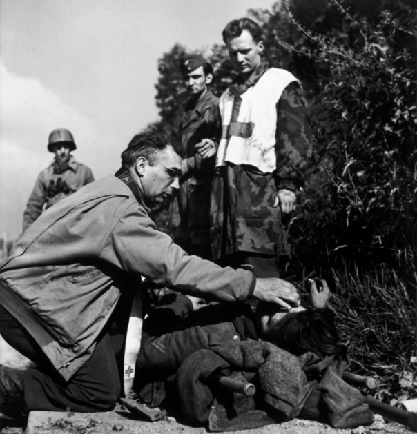 FRANCE. June/July, 1944. An American chaplain comforts a dying German soldier as prisoners of war look on.