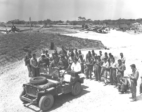 """Chaplain Joseph J. Garrity conducts the first Catholic services on Yontan airfield, Okinawa, 16 April 1945. The Hell's Belles fighter squadron of MGen Francis P. Mulcahy"""