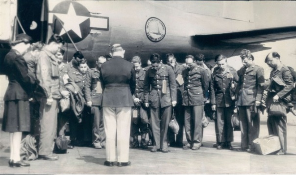 """The first group of soldiers to return to the United States after news of the surrender of Germany, bow their heads in prayers offered by Capt. Edward J. Barber, Chaplain at the air transport command base at La Guardia field. All of the men were wounded in European campaigns. (AP Wirephoto from Air Transport Command)."""
