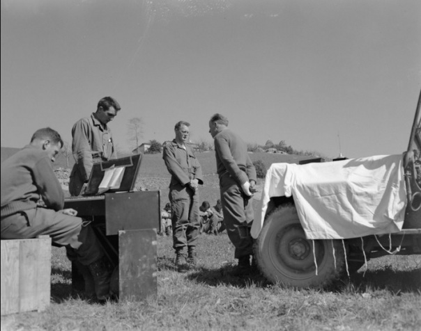"""April 1, 1945. Protestant Easter Service in Appennines, Italy background are trees and buildings.; Members of the Tenth Mountain Division, 605th Artillery Battalion, attend a Protestant Easter religious service at Rocca Pitigliano, Italy, conducted by Chaplain William H. Bell. In the foreground, four men bow their heads together. Corporal Ralph Squires sits at a portable organ and two soldiers face the Chaplain who stands in front of his jeep draped with a white cloth in use as an altar for a small crucifix."""