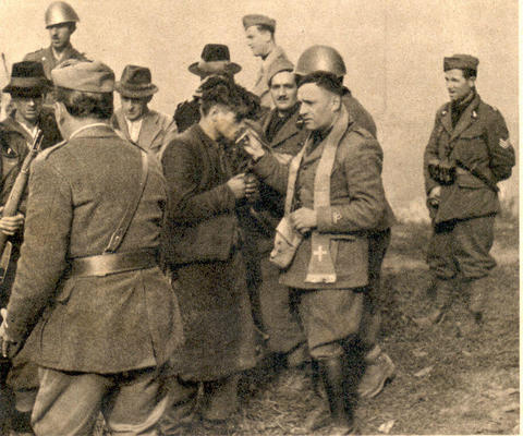 A Yugoslav partisan kisses the cross of a Black Shirts chaplain after last confession