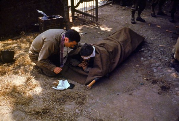An-American-Army-chaplain-kneels-next-to-a-wounded-soldier-in-order-to-administer-the-Eucharist-and-Last-Rites-France-1944