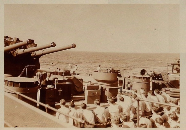 1940s, chaplain leads worship on the deck of ship in the shadow of the guns.