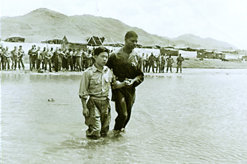 "Korean soldier Lee Hyeong-hwan receives baptism with the guidance of U.S. Army officer Hubert Engram, near Seoul, around August 1952. The Institute for Military History said, ""Looking at Lee's clothes, he must have been a civilian attached to the U.S. 8th Army, or an interpreter."""
