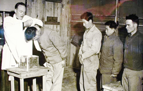 U.S. Navy chaplain Alexander Boyer baptizes a Korean worker employed at his base, in the winter of 1952.